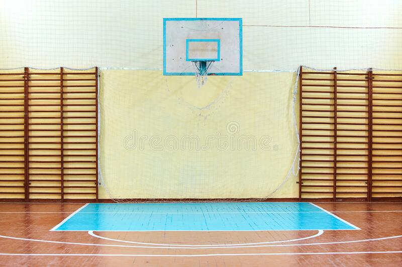 Gym for sports classes at school or College. Swedish wall, stairs, and wooden floor with markings for volleyball.  royalty free stock photo