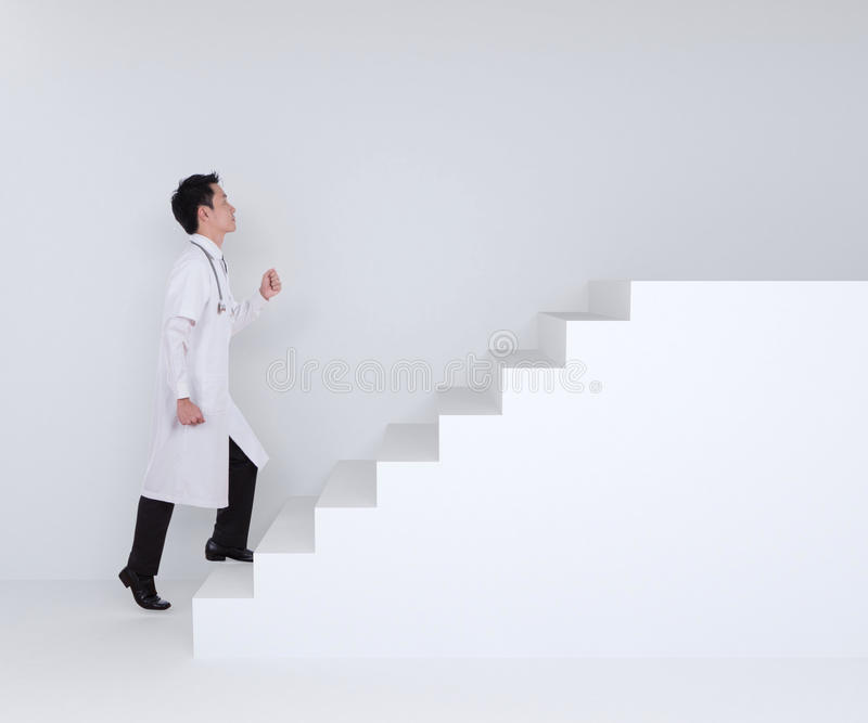 Male doctor stepping up on stairs royalty free stock photos